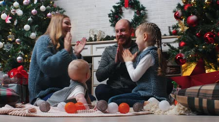 díszített : New Year - happy family playing pat a cake with each other