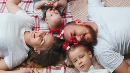 szenteste : New Year - family is lying on a blanket talking and smiling