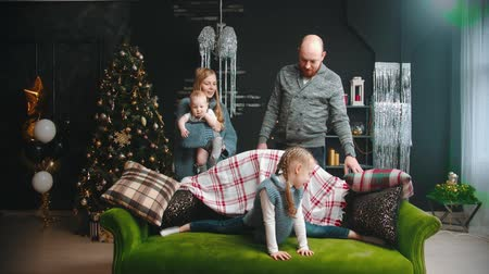 father christmas : Christmas concept - a little girl sitting in a split on the couch and her family watching her