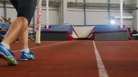 pigtailler : Pole vaulting indoors - young woman with pigtails preparing for the jump - running up