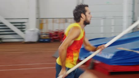 résztvevő : Pole vaulting indoors - a man in yellow shirt performing a jumping over the bar Stock mozgókép