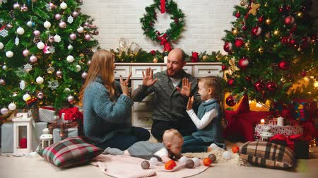 pat : NEW YEAR - the family in New Years atmosphere are playing pat-a-cake near the Christmas tree Stock Footage