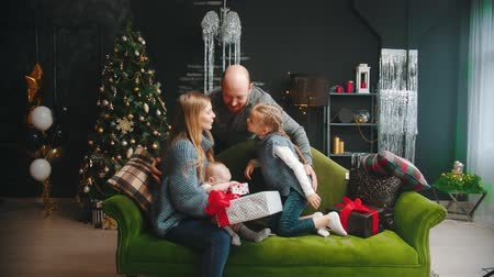 beso : Christmas concept - wife and daughter kiss the man and husband in the cheeks and a girl hugs her dad Archivo de Video