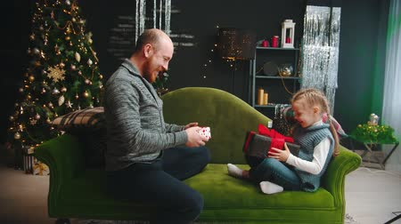 díszített : Christmas concept - a dad with daughter exchanging gifts on christmas Stock mozgókép
