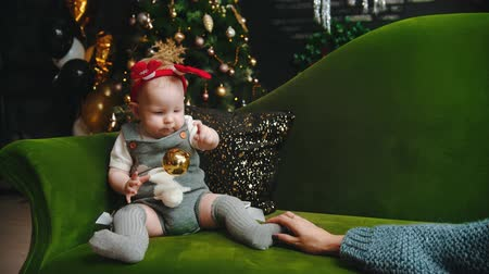 christmas tree decoration : NEW YEAR - baby is sitting on sofa and playing with christmas ball