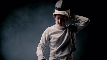 armas : Fencing training - young woman fencer walking out from the dark and putting on a protective helmet - gets into position and starts fighting