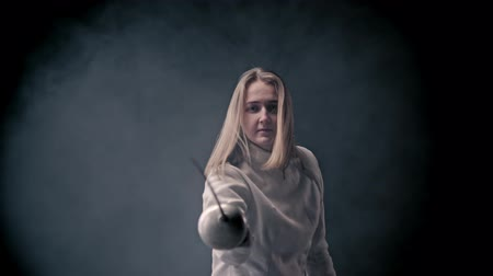 saber : Fencing training - young woman fencer with long hair walking out from the dark - gets into position and starts fighting
