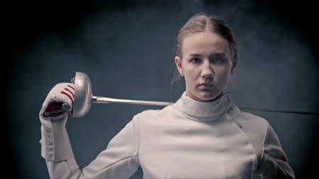 saber : Fencing training - A young woman fencer walking out from the dark and putting the sword behind her shoulders