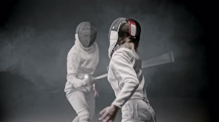 rivalidade : Fencing training - two young woman having a duel between each other