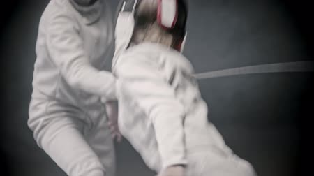 szermierka : Fencing training - two young women in protective clothes having a duel between each other