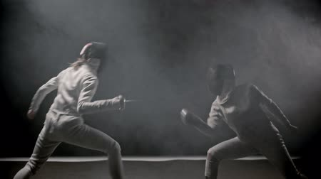 armas : Fencing training - two young women having a duel between each other in the smoky studio Archivo de Video