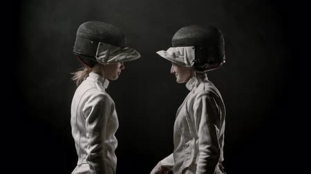 saber : Fencing training - two young women walking off the dark and greeting each other before the duel