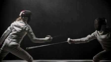 saber : Fencing training - two young women having a duel between each other in the dark smoky studio
