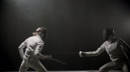 фехтование : Fencing training indoors - two young women having a duel between each other in the dark smoky studio