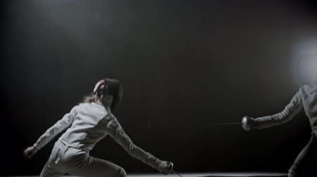 armas : Fencing training - two young women having a duel between each other in the dark smoky studio