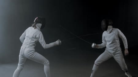 saber : Fencing training in the dark studio - two women having a duel