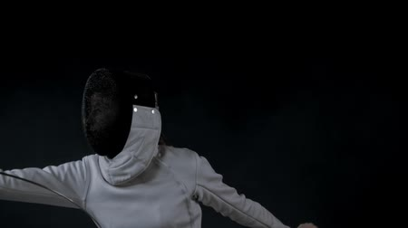 saber : Fencing training in the studio - young woman in white costume having a duel Stock Footage