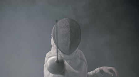 hekje : Fencing training in the studio - young woman fencing in the smoke Stockvideo