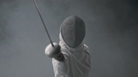 armas : Fencing training in the dark studio - young woman fencing in the smoke