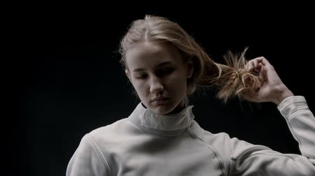 saber : A young woman fencer lets her hair down and shakes her head up and down