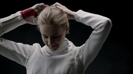 saber : A young woman fencer putting her hair up into a bun before the training Stock Footage