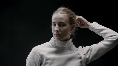 armas : A young attractive woman fencer lets her hair down and shakes her head