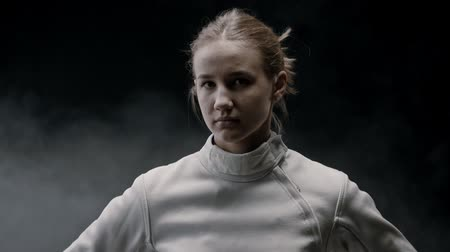 saber : A young pretty woman fencer in the smoky studio