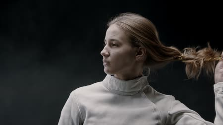 saber : A young woman fencer lets her hair down and shakes her head