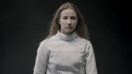 szermierka : A young woman fencer standing in the studio with a sword behind her shoulders