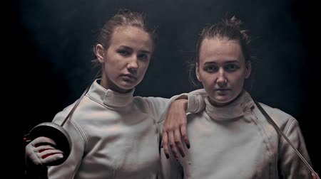 囲い : Two young women fencers standing in the dark studio - posing - raising their heads up and looking in the camera