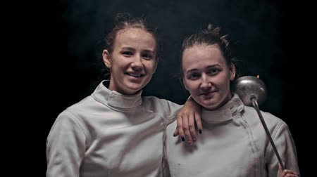 armas : Two young women fencers standing in the dark studio - looking in the camera