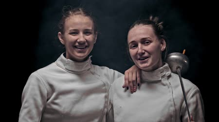 armas : Two young women fencers standing in the studio and looking in the camera Archivo de Video