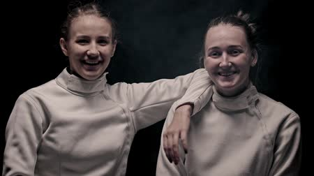 ライバル : Two young smiling women fencers standing in the studio and looking in the camera
