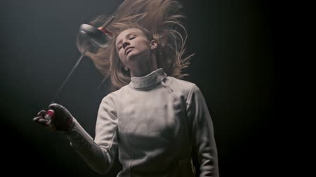szermierka : A young attractive woman fencer playing with her sword Wideo