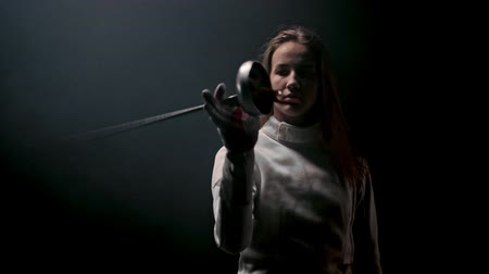 rivalidade : A young attractive woman fencer playing with her sword in the dark Stock Footage