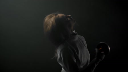 saber : A young woman fencer with long hair playing with her sword in the dark studio Stock Footage