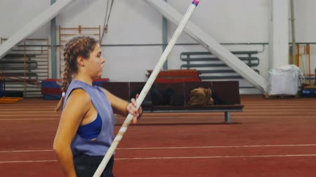 pigtailler : Pole vaulting indoors - young woman with pigtails preparing for the jump - running up - jumping over the bar