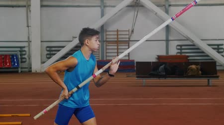 participante : Pole vaulting indoors - a young man in blue shirt breathing in and out and starts running up before jumping