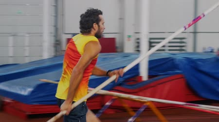 participante : Pole vaulting indoors - a man in yellow shirt running up and jump over the bar
