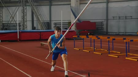 participante : Pole vault training - a young man in blue shirt breathing in and out and starts running up before jumping Vídeos