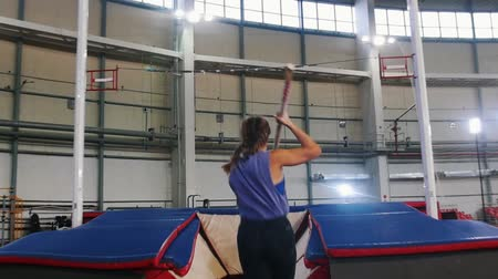 pigtailler : Pole vaulting in the indoors stadium - young woman with pigtails jumping over the bar and falling down