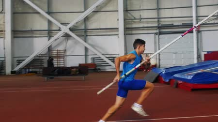 participante : Pole vault training - a young man in blue shirt jumping over the bar and touches it