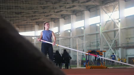 elevação : Pole vaulting in the indoors stadium - young woman with pigtails raises up the pole and starts running Stock Footage