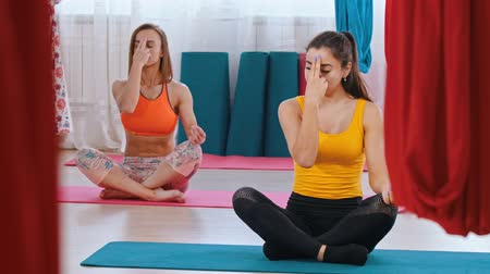 hängematte : Yoga - two women sitting on the mats and doing breathing exercises with two fingers on the forehead