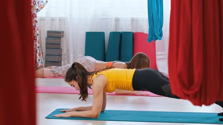 pozisyon : Yoga - two women holding a plank in the bright studio Stok Video