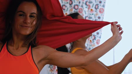 pozisyon : An athletic woman playing with red hammock for yoga - wraps herself in a cloth - her trainer working on the background Stok Video