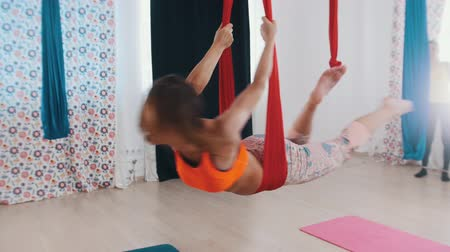 pozisyon : Aerial yoga - an athletic woman hanging in hammock for yoga and having fun