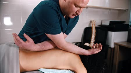 chiropraxie : Chiropractic treatment - the doctor giving a woman patient a massage for the spine - pushing on the back with his elbows