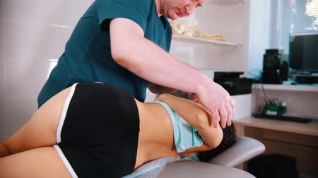 presleme : Chiropractic treatment - doctor moving the woman the side and pressing on her back Stok Video