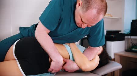 ajustando : Chiropractic treatment - doctor moving the woman the side and pressing on her back - exercises for the spine